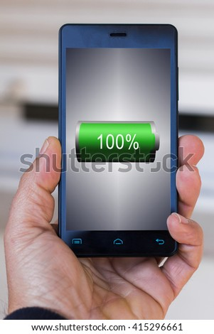 A man holding mobile smartphone in outdoor with full battery icon at screen