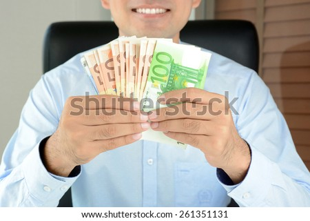 A man holding money,Euro currency(EUR), with smiling face