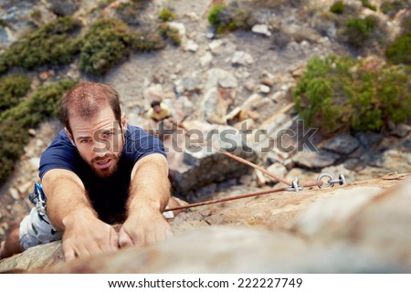 A man holding on to a piece of rock while he climbs up a steep cliff with copyspace - stock photo