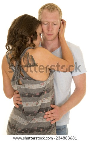 a man holding on to his woman close, she has an owl tattoo on her shoulder. - stock photo