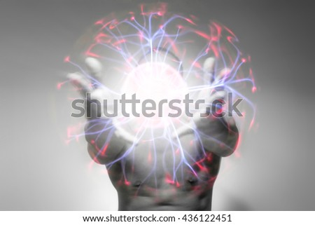 A man holding out a colorful plasma ball in his hand for the concept: Renewable Energy.  - stock photo
