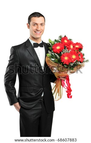 A man holding out large bouquet of gerberas in formal black tux with bow tie isolated on white background - stock photo