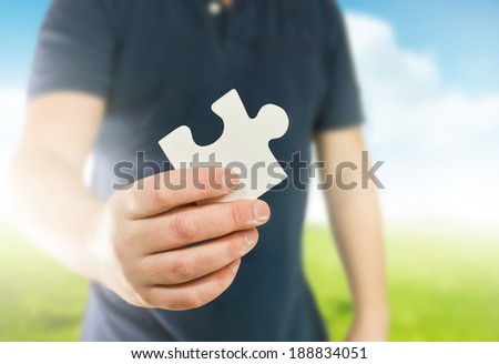 A man holding the missing puzzle piece. - stock photo