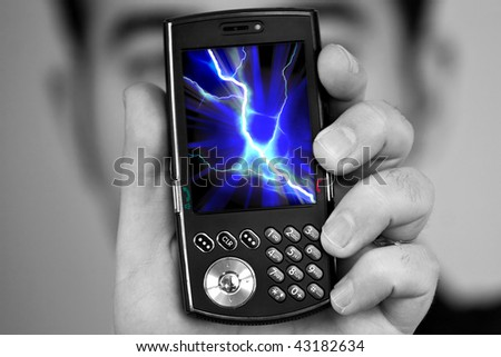 A man holds a cell phone with a lightning bolt illustration on the screen.  Great image to illustrate cell phone radiation. - stock photo