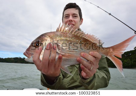 A man holds a fish that he caught during fishing at sea on a fishing boat. - stock photo