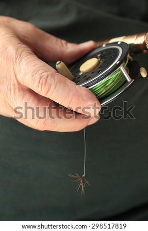 A man holds a fly fishing rod and reel with fly attached, copy space included - stock photo