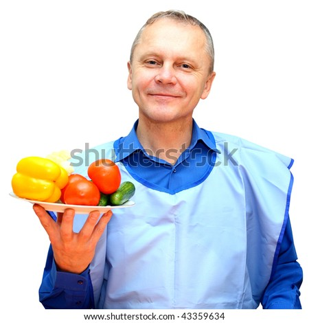A man holds a plate of vegetables on an isolated background. - stock photo