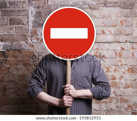 A man holds a sign forbidding face. - stock photo