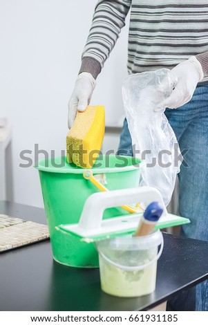 A man holds a sponge above a bucket next to a putty bucket and a spatula