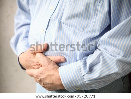 a man holds both hands to his stomach - stock photo