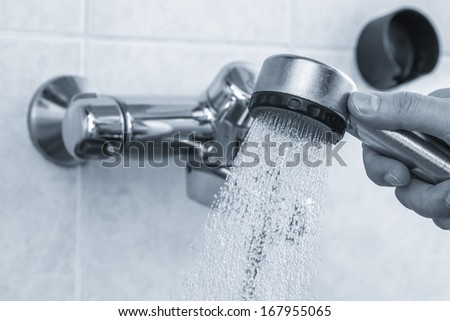 A man holds open shower mixer in bathroom, tinted black and white image, horizon format - stock photo