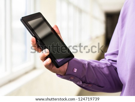 A man holds up and running on a Tablet PC - stock photo