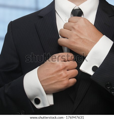 A man in a black suit straightens his tie - stock photo
