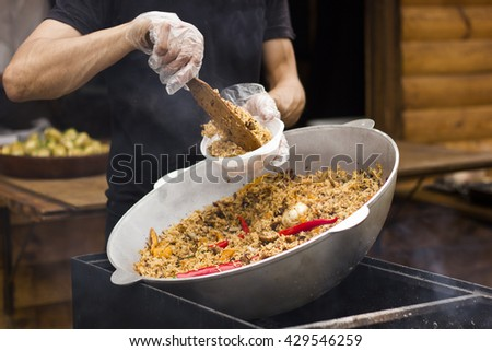 A man in a black T-shirt puts in a plastic dish pilaf. Pilaf is a great dish and cooked on a grill outdoors.
