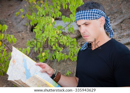 A man in a black T-shirt with a map in hand - stock photo