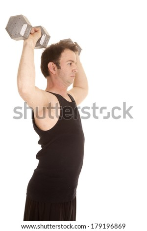 A man in a black tank top lifting big weights from the side. - stock photo