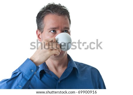 A man in a blue dress shirt, drinking from a small cappuccino / coffee cup, isolated on white. - stock photo