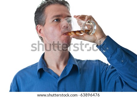 A man in a blue dress shirt, drinking pop from a glass with ice, isolated on white.