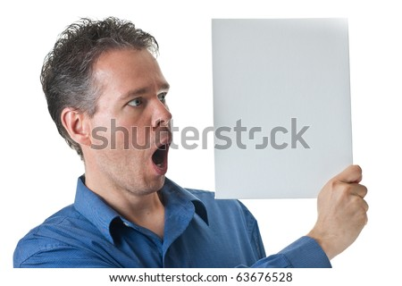 A man in a blue dress shirt, holding a blank white sign, with the look of surprise on his face, isolated on white. - stock photo