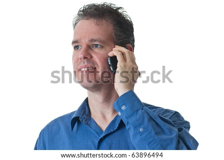A man in a blue dress shirt, talking on a cellular phone, isolated on white.