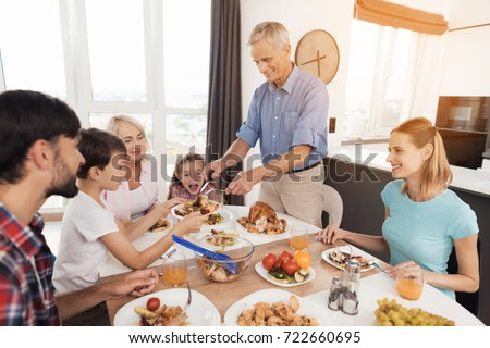 A man in a blue shirt spreads his baked turkey to his relatives. The family sits next to the holiday table for Thanksgiving