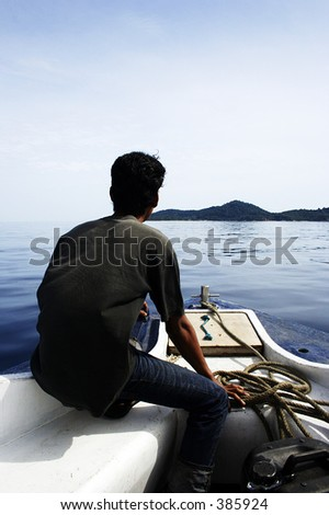 A man in a boat heading to island.