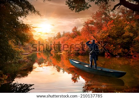 A man in a boat on the river in the autumn