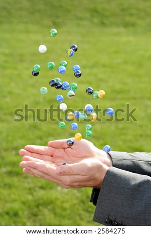 A man in a business suit catching many falling marbles outdoors - stock photo