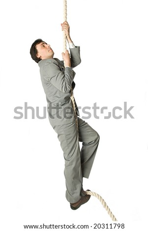 A man in a business suit climbing a rope - stock photo