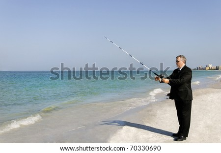 A man in a business suit fishing at the ocean. - stock photo