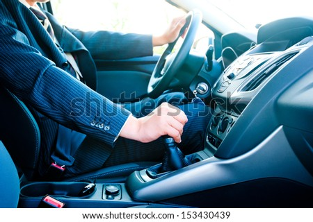 a man in a business suit in the car changes gear - stock photo