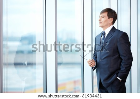 A man in a business suit looks out the window - stock photo