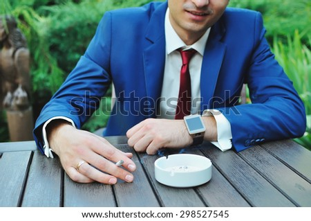 A man in a business suit relaxing outdoors in summer cafe at the wooden table. Male smokers . Photographed with shallow depth of field. The only field hand with a cigarette. - stock photo