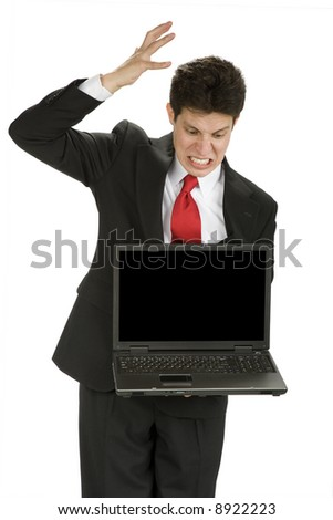 A man in a business suit showing his frustration or anger at a laptop he is holding.