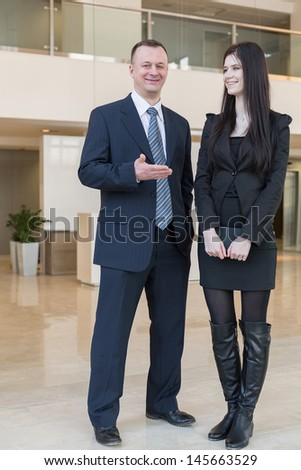 A man in a business suit shows his hand on a woman with a notepad