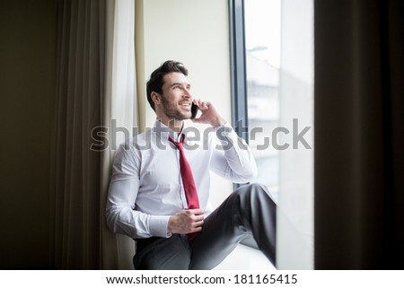 A man in a business suit sitting next to window and talking with mobile phone - stock photo