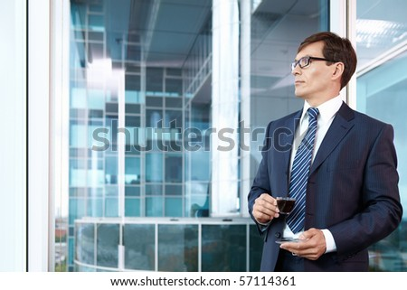 A man in a business suit with a cup of coffee - stock photo