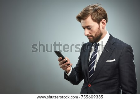 A man in a business suit with a smartphone. Studio portrait.