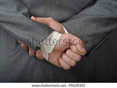A man in a business suit with his hands behind his back. - stock photo