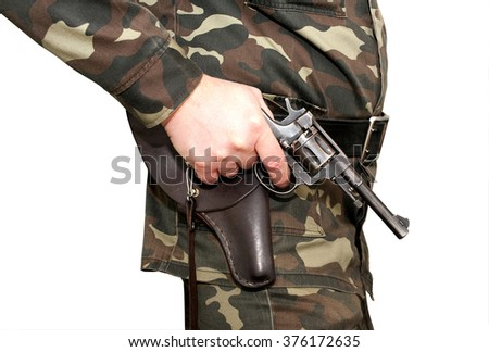A man in a camouflage uniform with his right hand holding a revolver near the holster and holding your finger on the trigger, ready to fire - stock photo