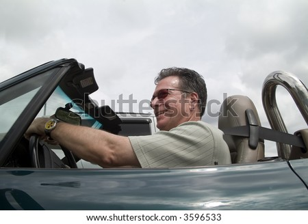 A man in a convertible sports car driving with the top down and passing a car. - stock photo