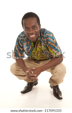 A man in a crouch with a smile on his face. - stock photo