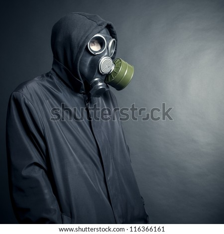 A man in a gas mask on a black background - stock photo
