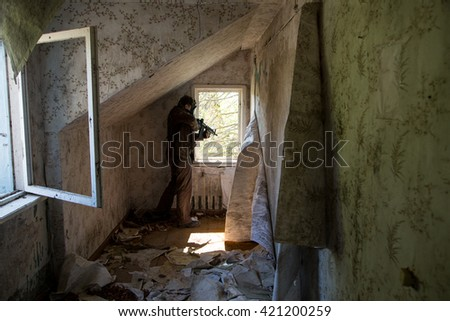 a man in a gas mask with a gun, in house beside with window