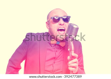 A man in a gray jacket, bow tie and sunglasses singing with a microphone in his hand. Toned - stock photo