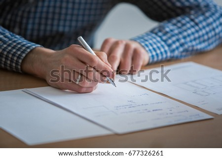 A man in a gray shirt puts a signature on paper The manager signs the documents The head holds a pen in his hands A business man in a suit makes calculations on the calculator