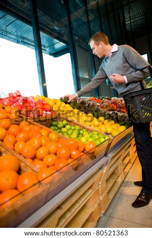 A man in a grocery store buying fruits and vegetables - stock photo