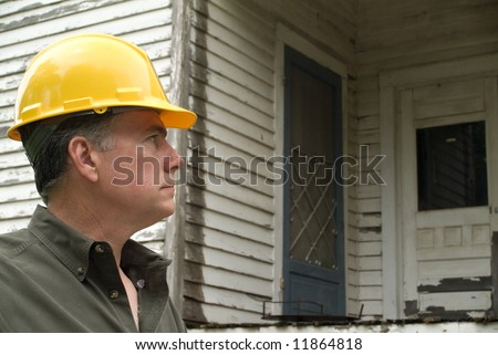 A man in a hard hat looking at an old rundown house. - stock photo