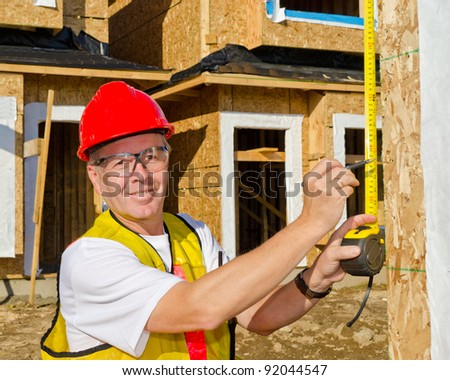 A man in a hard hat standing in front of an house at sunny day holding a measure tape in his hand. - stock photo