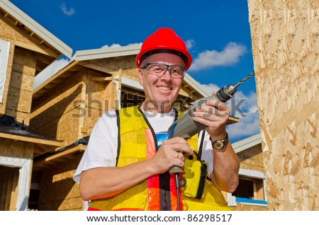 A man in a hard hat standing in front of an house holding a drill in his hand. - stock photo